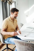 Happy Mature Man Turning Page Of Newspaper On Table At Home