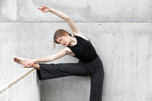 Dancer In Black Striped Pants Stretching In Front Of Concrete Wall
