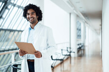 Cheerful Young Male Healthcare Worker Holding Clipboard While Standing In Corridor At Hospital