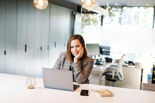 Smiling Businesswoman With Hand On Chin Using Laptop At Desk In Office