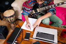 Young Man With Guitar Writing Notes On Book By Laptop In Living Room