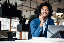 Smiling Businessman Talking On Telephone While Sitting With Laptop At Office