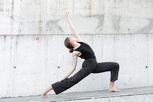 Dancer In Black Striped Pants In Front Of Concrete Wall