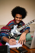 Happy Male Guitarist With Guitar Writing Musical Notes In Book On Table At Home