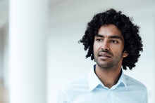 Thoughtful Young Male Entrepreneur With Curly Black Hair Looking Away At Office