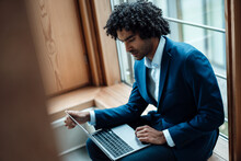 Young Male Professional Using Laptop While Sitting Against Window At Office