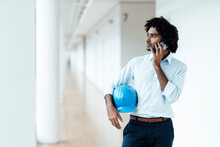 Young Male Architect With Hardhat Looking Away While Talking On Mobile Phone In Corridor At Office