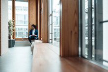 Young Businessman Sitting Against Window In Office