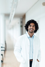 Smiling Young Male Doctor Standing With Hands In Lab Coat Pockets At Hospital Corridor