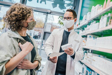 Pharmacist Recommending Medicine To Smiling Customer In Chemist Shop
