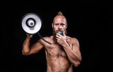 Male Viking Talking Through Megaphone Against Black Background In Studio