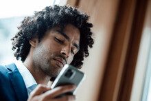 Young Male Entrepreneur With Curly Black Hair Using Smart Phone At Office