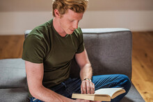 Mid Adult Man Reading Book While Sitting On Couch At Home