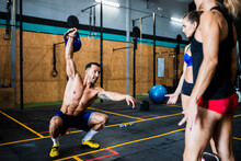Male Fitness Instructor Lifting Kettlebell And Practicing Squats While Assisting Women In Gym