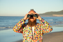 Smiling Man Looking Through Binocular While Standing Against Sea