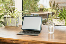 Digital Tablet With Keyboard By Glass On Table At Home