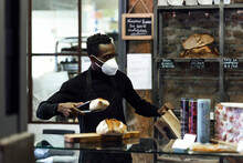 Salesman Wearing Face Mask Packing Bread While Standing At Bakery