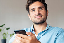Man With Blue Eyes Looking Away While Using Mobile Phone At Home