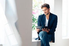Businessman Using Digital Tablet While Sitting On Window Sill At Home