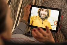 Mature Woman Using Digital Tablet For Video Chat In Living Room