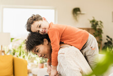 Mother Piggybacking Smiling Son While Sitting At Home