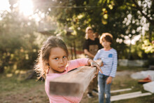Girl With Brother And Mother Carrying Wooden Plank In Yard