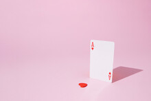 Playing Card Ace Of Hearts On Pink Pastel Background With A Lonely Heart Separated From The Middle. Flat Lay Minimal Concept. Valentines Day Inspiration. Layout Design. Gambling Mood.
