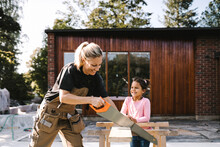 Smiling Daughter Looking At Mother Cutting Plank With Hand Saw Against House