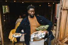 Smiling Man Balancing Food While Standing At Doorway During Social Gathering