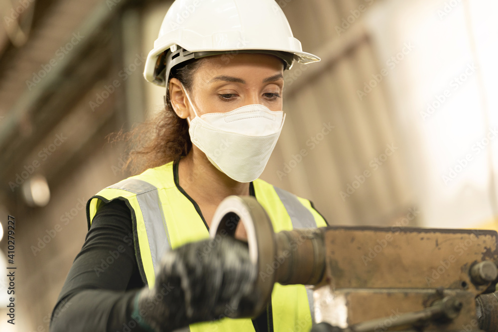 Fototapeta workers factory Brazilian woman wearing Face Shield mask and working at heavy machine. Safety protection of air pollution smoke dust and disease virus Covid 19. New normal life in workplace.