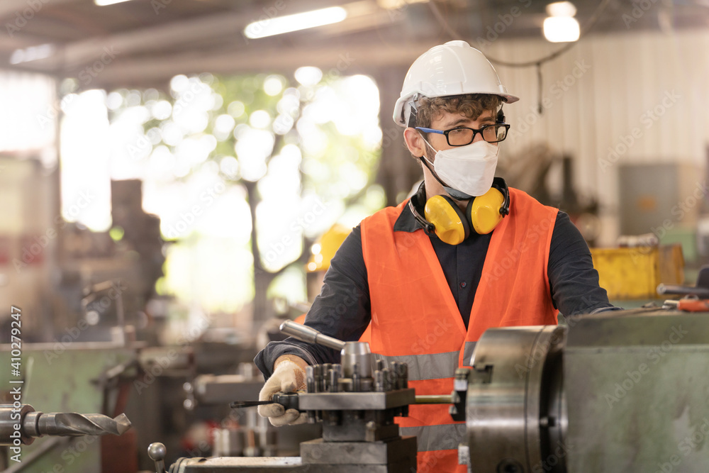 Fototapeta workers factory man wearing face mask and working at heavy machine. Safety protection of air pollution smoke dust and disease virus Covid 19. New normal life in workplace.