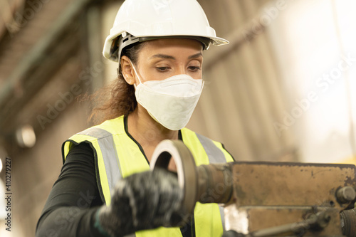 Obraz workers factory Brazilian woman wearing Face Shield mask and working at heavy machine. Safety protection of air pollution smoke dust and disease virus Covid 19. New normal life in workplace. - fototapety do salonu