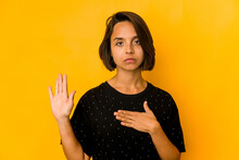 Young Hispanic Woman Isolated On Yellow Taking An Oath, Putting Hand On Chest.