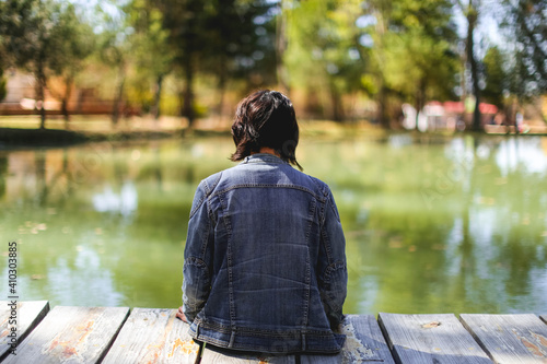 Canvas Print Woman  woth a denim jackt relaxing on wooden dock by a beautiful lake