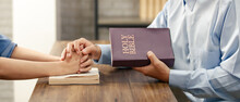 Close Up Hand. Asian Man Holding A Bible And A Woman's Hand Is A Sign Of Love For Jesus Or God. According To The Beliefs Of Christianity. Concept Believe Love Prayer..