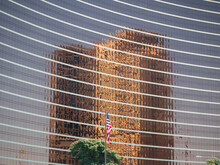 Copper Colored High-rise Reflecting On Another High-rise With American Flag.