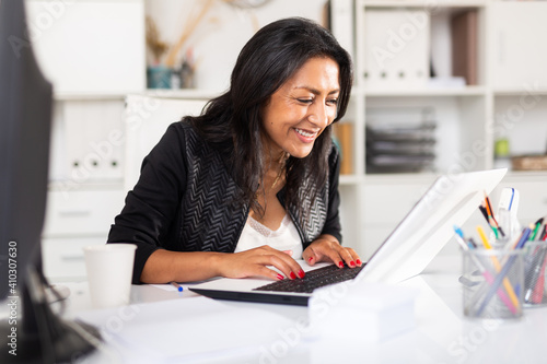 Smiling successful hispanic business woman working on laptop in modern office