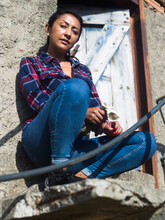 Portrait Of Young Latino Woman At Doorway Of Old Countryside Building