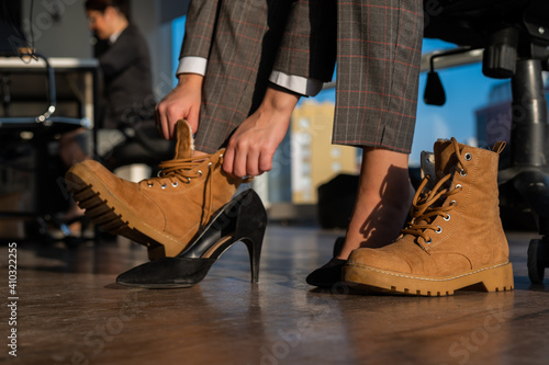 Tablou Canvas Business woman changes shoes with high heels on boots in the office