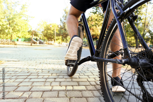 Male cyclist riding bicycle outdoors, closeup Fototapeta