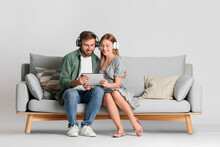 Young Couple With Tablet Computer And Headphones On Sofa Against Light Background
