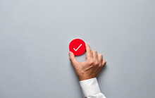 Businessman Hand Holding A Red Badge With A Check Mark. Approve, Verify Or Confirm In Business