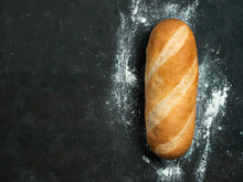 British White Bloomer Or European Baton Loaf Bread On Black Background. Top View Or Flat Lay. Copy Space For Text Or Design