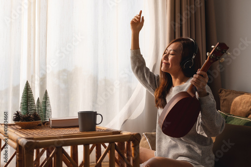 A beautiful young asian woman with headphone enjoy playing an ukulele at home
