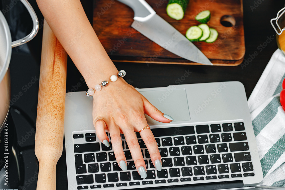 Fototapeta Female using laptop while cooking in kitchen close up