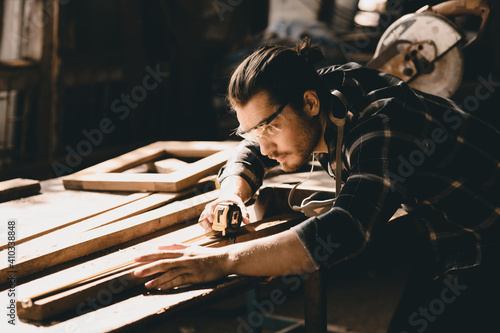 Obraz Carpenter man attend to making masterpiece woodworks handcrafted furniture fine measure in wood workshop. - fototapety do salonu