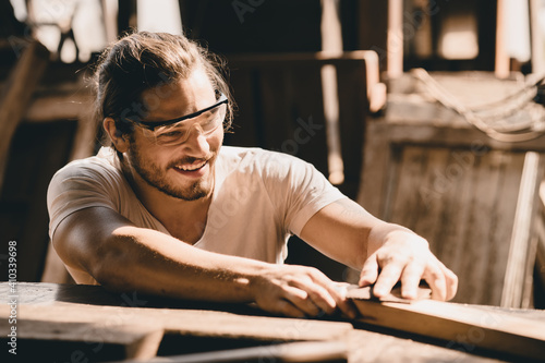 Obraz Young Carpenter happy working to making woodcraft furniture in wood workshop look professional high skill real people workman. - fototapety do salonu