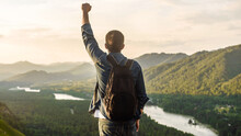A Hiker Man With A Backpack Stands In A Winner's Pose With A Raised Hand On The Top Of A Mountain. Travel And Vacation Concept. Trekking Or Victory