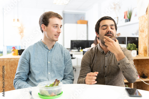 Fotografia, Obraz A man with a salad looking with envy to his coworker eating a sweet food in the office