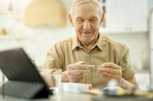 Cheered-up elderly man having a close look at syringe Tapéta, Fotótapéta
